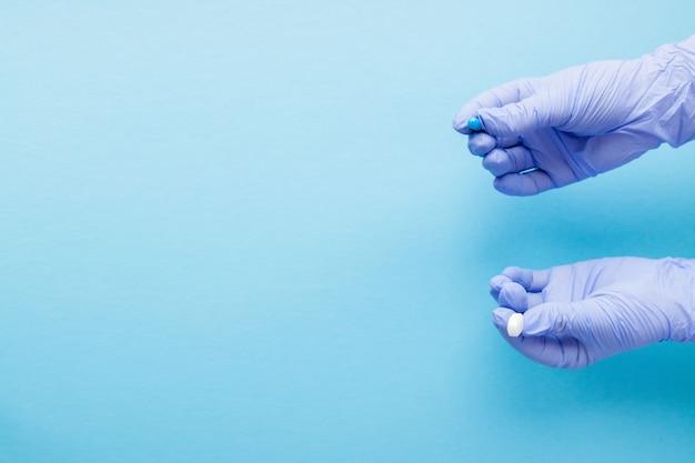女性は2つの大きな錠剤を与える医療用手袋を手します。青と白。選択してください。コピースペース