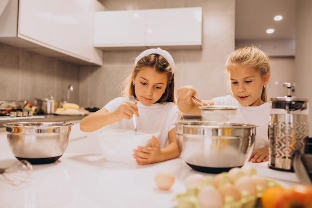 キッチンで料理をする2人の少女姉妹