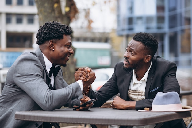 Бизнесмен 2 африканцев сидя вне кафа