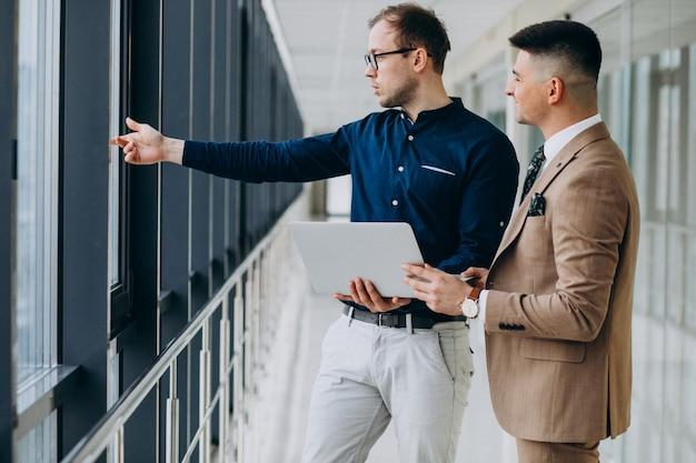 ノートパソコンで立っているオフィスで2人の男性の同僚