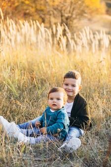 フィールドに一緒に座っている2つの小さな赤ちゃん兄弟