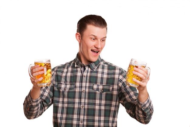 探しているハンサムな男は、白で隔離されるビールを2杯を持って興奮しています。魅力的な幸せな男笑顔で笑って、飲み物でポーズ