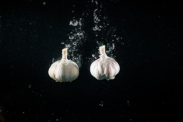 ニンニクの2つのピースは水に落ちる泡を作る