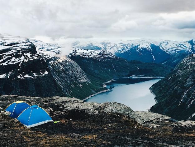 豪華な山の前に2つの青いテントが立っています