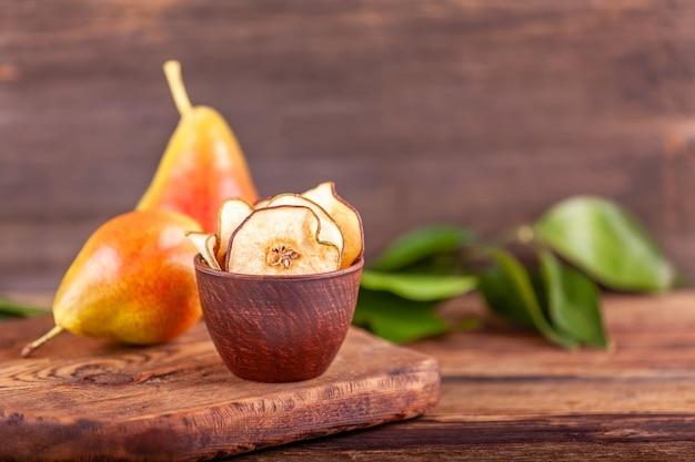 木製の背景に乾燥したチップを持つ2つの新鮮な赤梨