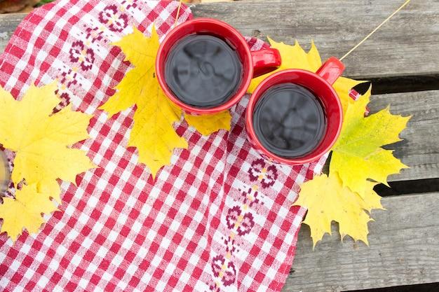 秋の黄色いシートに2つの赤いカップ