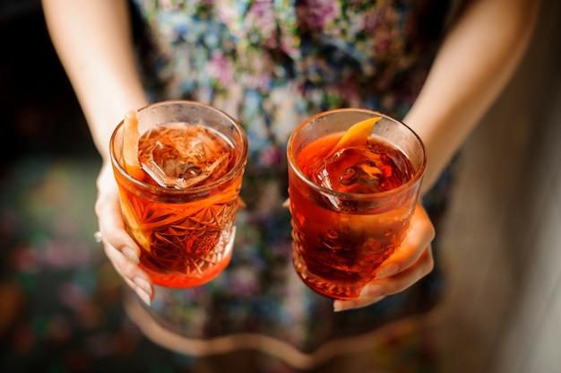 アルコールカクテルと2つのメガネを保持している女性の手