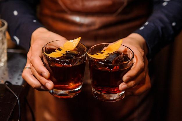 アルコール飲料で満たされた2つのメガネを保持しているバーテンダー