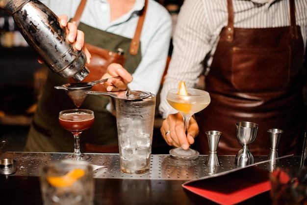 シェーカーとストレーナーを使用して、バーカウンターのエプロンで2人のバーテンダーが氷でアルコールカクテルを準備します。