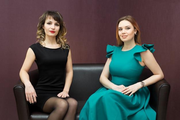 ソファの上の2人の魅力的な若い女の子。