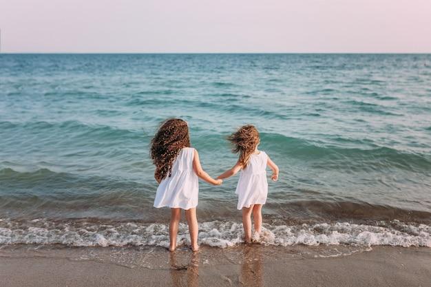 白いドレスの2人の女の子が海の泡でビーチに立っています。