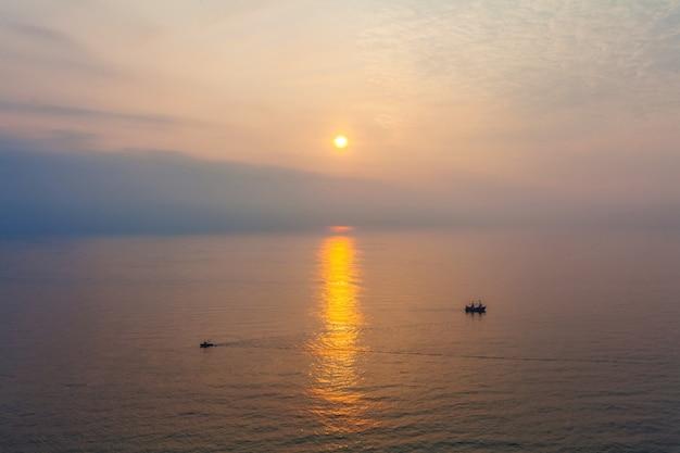 日没時に海で2つのボート