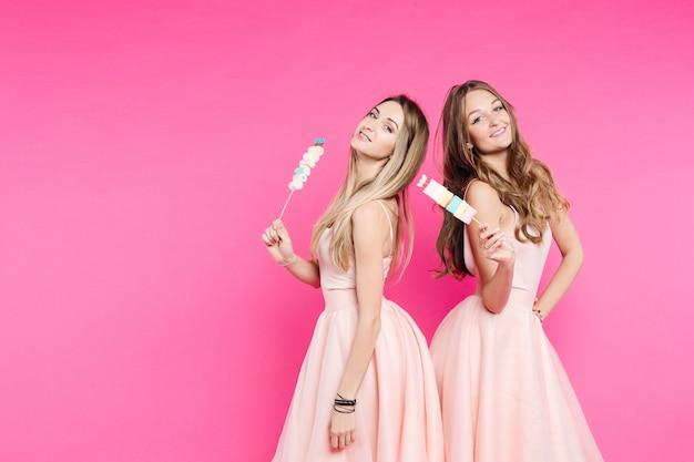 マシュマロとピンクでポーズをとる人形のような2つの甘い女の子。