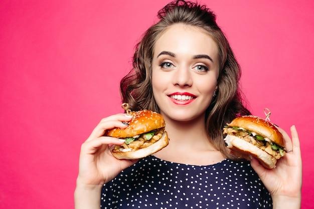 ポジティブな女の子笑顔と2つのおいしいハンバーガーでポーズします。