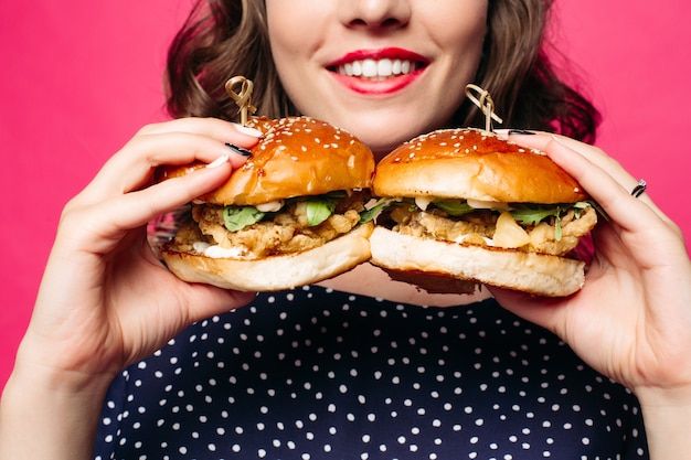ジューシーなチキンとサラダの2つのハンバーガーの広告。