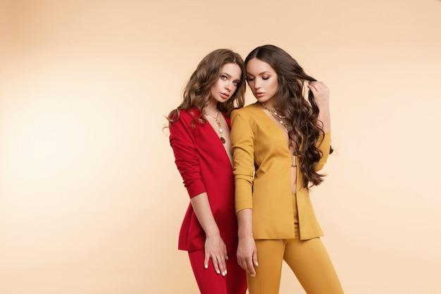 明るいスーツのポーズで2つの豪華なモデル