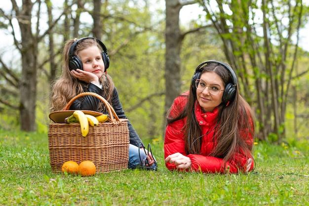 晴れた春の日に、ピクニックバスケットの近くの公園で2人の姉妹が芝生で休んで音楽を聴く