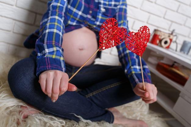妊娠中の女性は、手で2つのおもちゃの心を保持しています。