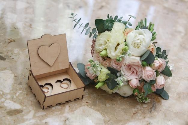 美しい木製の箱に2つの金の結婚指輪。ピンクと白の花のウェディングブーケ。結婚式の日。結婚式の詳細。