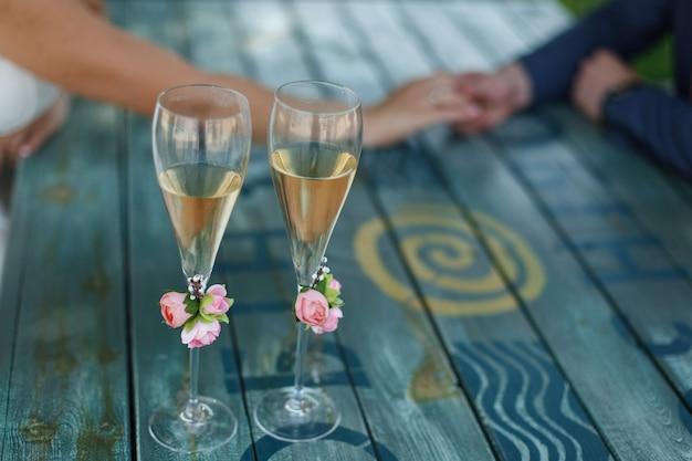 結婚式の日のテーブルでシャンパンと2つの装飾が施されたメガネ。お祝いの場所。