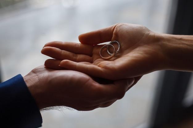 新婚夫婦の手にある2つの結婚指輪がクローズアップ。結婚式。結婚式の日。ロマンチックな瞬間。カップルは結婚指輪を交換します。ちょうど夫婦。
