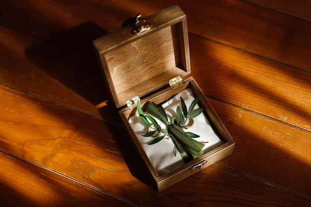テキストのコピースペースを持つ木箱に2つの黄金の結婚指輪をクローズアップ。木製に分離された結婚指輪。結婚式の日。結婚式の詳細。物語のコンセプトが大好きです。結婚式