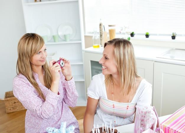 キッチンで誕生日パーティーの間に写真を撮っている2つの輝く女性の友人