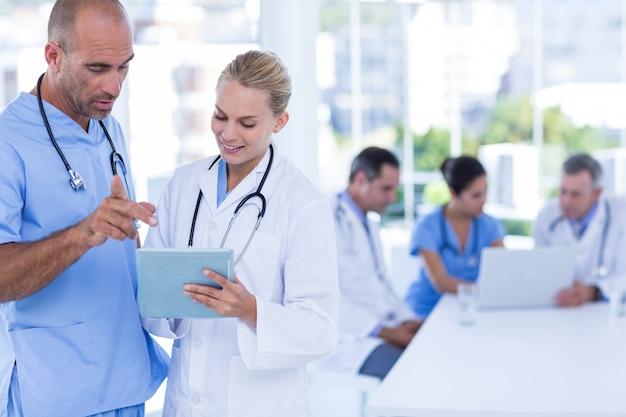 クリップボードを見ている2人の医者、仕事中の同僚