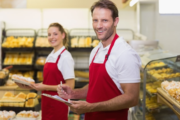 カメラを見ている2つの笑顔パン屋の肖像