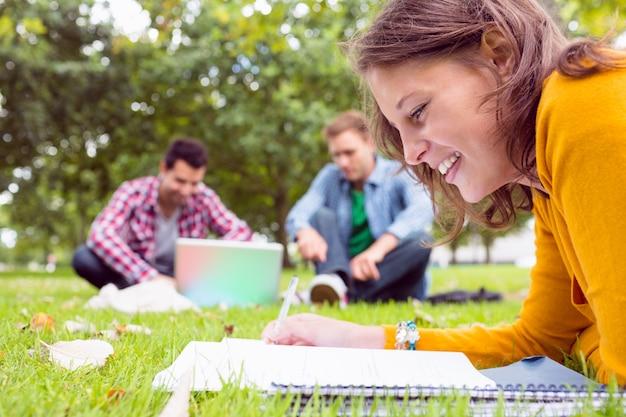 公園でラップトップを使用している2人の学生がノートを書く