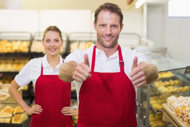 親指で2人のパン屋の笑顔の肖像