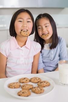 キッチンでクッキーと牛乳を楽しむ2人の女の子