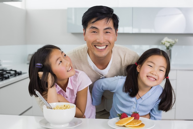 幸せな2人の娘とキッチンで朝食をとっている笑顔の男