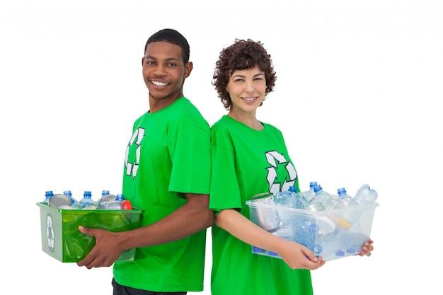 リサイクル可能な箱を持ち、背中合わせに立っている2人の活動家