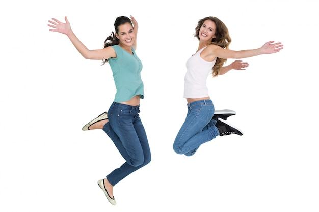 2つの明るい若い女性の友人ジャンプ
