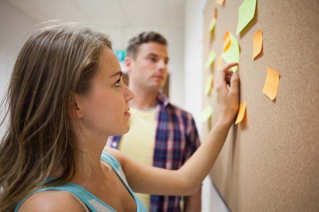 掲示板を見ている2人の学生