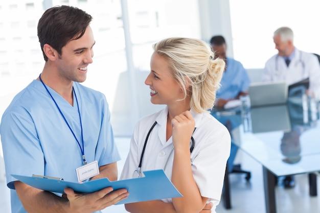 青いファイルについて話している2人の若い医者