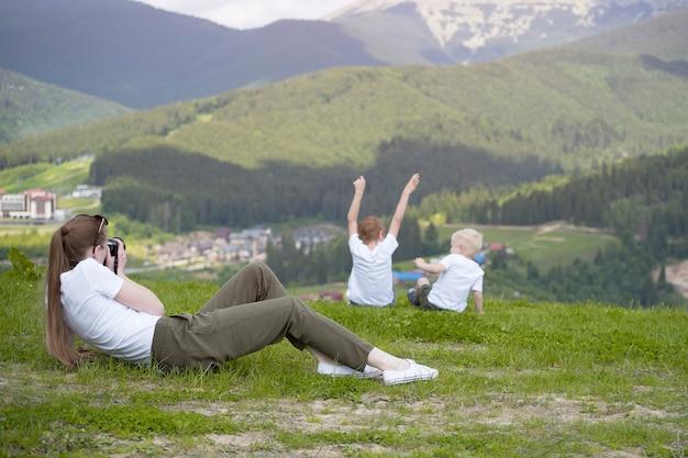 若い女性が2人の若い男の子の写真を撮る。背面図。山