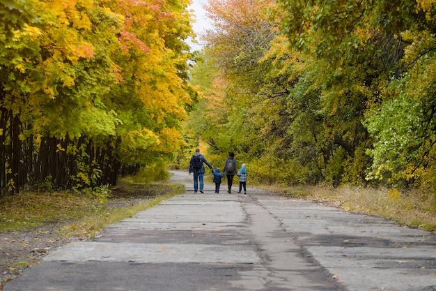秋の公園で2人の息子を持つ家族が歩いています。