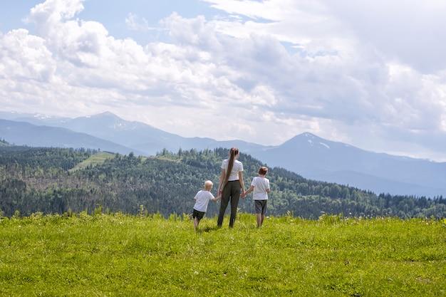 母と2人の幼い息子が緑の野原に手を取り合って立っています。