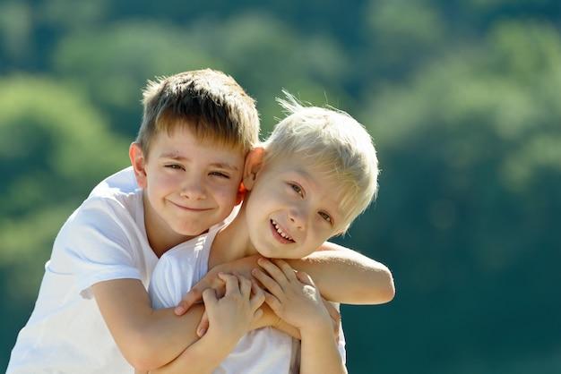 2人の男の子が屋外で抱いています。友情と友愛の概念