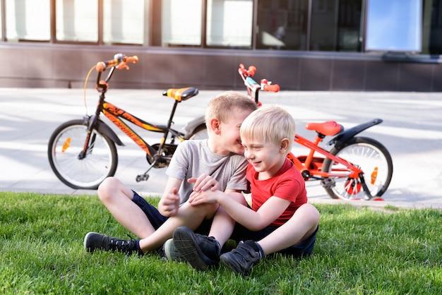 2人の少年は、草の上に座って通信します。サイクリング後の休憩、バックグラウンドでの自転車