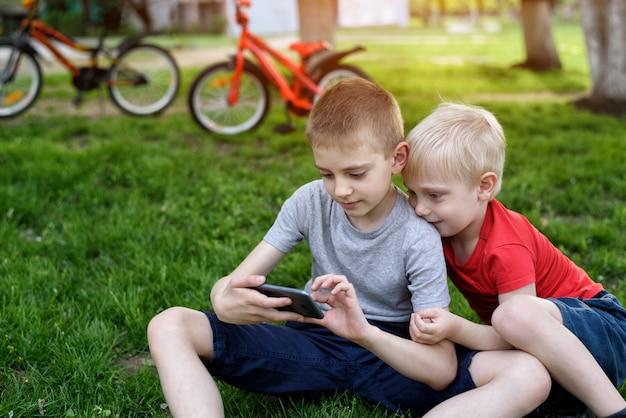 2人の男の子が草の上に座ってスマートフォンでゲームをしています。