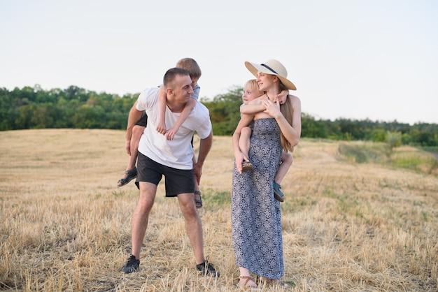 幸せな若い家族。父親、妊娠中の母親、背中にいる2人の小さな息子。斜めの麦畑。日没時間