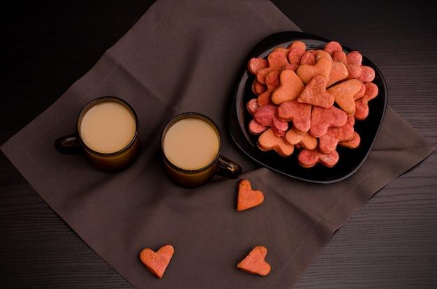 ハート型のコーヒーの2つのマグカップとクッキーの黒いプレート、バレンタインの日