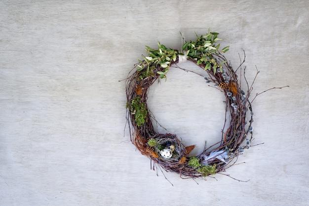 灰色の漆喰の壁に柳の小枝をかぶった花輪に2つの卵がある鳥の巣。真上