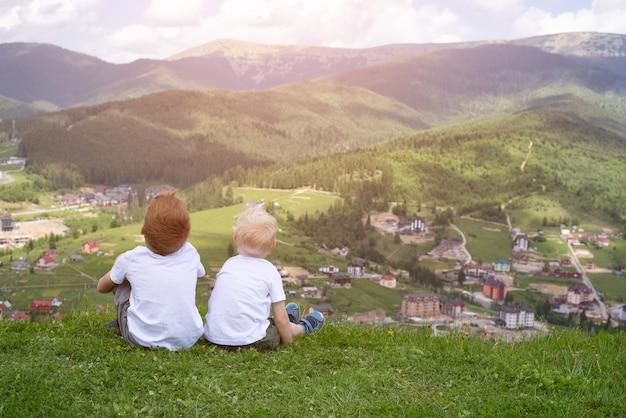 2 мальчика сидя на холме и смотря горы. вид сзади