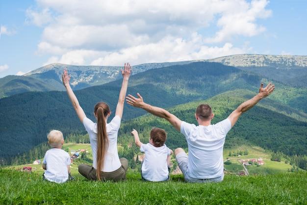 家族の休日。両親と2人の息子が手を挙げて座っています。山の景色。背面図。