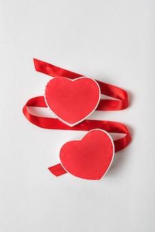 2つの赤いハート型のボックスとホワイトスペースにサテンのリボン。愛のシンボル、バレンタインデー。