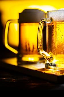 白い泡が付いている2つの軽いビールジョッキ